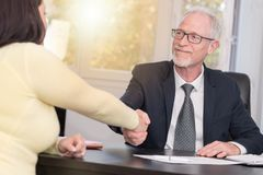 Adviser shaking hand with client after signing a contract, light effect Stock Photos