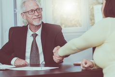 Adviser shaking hand with client after signing a contract, light effect Royalty Free Stock Photos