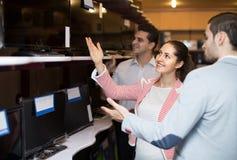 Adviseur die jong paar helpen om PC-monitor te kiezen stock foto