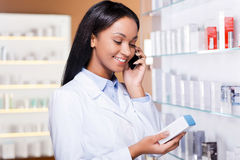 Advising a proper medicine. Beautiful young African woman in lab coat holding container with some medicine and talking on the mobile phone while standing in Stock Photo