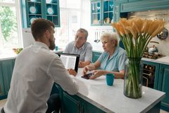 Advisor helps his elder clients. Giving a consultation in their dining room. Retirement planning or financial management royalty free stock photography