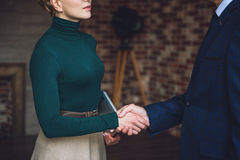 Advisor shaking hand of man. Focus on handclasp both businessman and woman. They are standing in room Stock Photos
