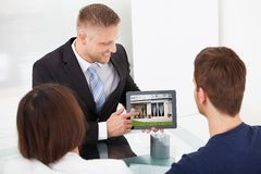 Advisor showing house picture to couple on tablet Royalty Free Stock Photos