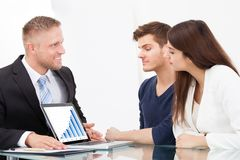 Advisor showing investment plans to couple on laptop Stock Images