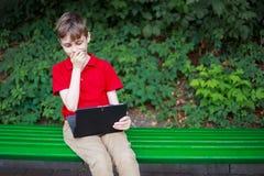 Advisory parental Muchacho pasmado que se sienta con la tableta en manos edu Imagenes de archivo