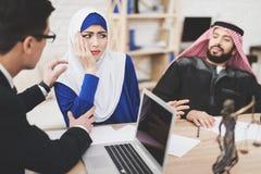 Advocaat in bureau met Arabische echtgenoot en vrouw De advocaat troost vrouw stock afbeelding