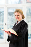 Advocaat in bureau met de lezing van het wetsboek door venster Stock Foto