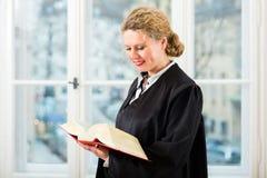 Advocaat in bureau met de lezing van het wetsboek door venster Stock Afbeeldingen
