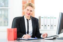 Advocaat in bureau met wetsboek die aan bureau werken stock afbeeldingen