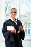 Advocaat in bureau met wetsboek en Dossier Stock Afbeelding