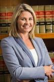 Advocaat die bij camera in wetsbibliotheek glimlachen Stock Foto