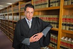 Advocaat die camera in de wetsbibliotheek bekijken Stock Afbeeldingen