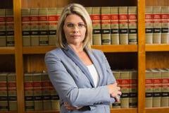 Advocaat die camera in wetsbibliotheek bekijken Stock Afbeeldingen