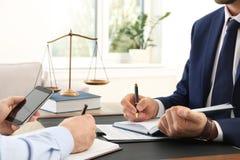 Advocaat die met cliënt bij lijst in offic werken stock afbeelding