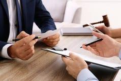 Advocaat die met cliënten bij lijst in bureau, nadruk werken royalty-vrije stock afbeeldingen