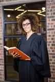Advocaat die zich dichtbij bibliotheek met wetsboek bevinden Stock Afbeeldingen