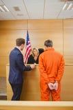 Advocaat en rechter die naast de misdadiger in jumpsuit spreken royalty-vrije stock afbeelding