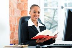 Advocaat in haar bureau met wetsboek op computer royalty-vrije stock foto