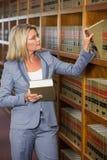 Advocaat het plukken boek in de wetsbibliotheek Royalty-vrije Stock Foto