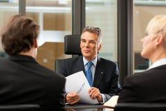 Advocaat of notaris met cliënten in zijn bureau Stock Fotografie