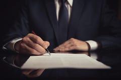 Advocaat, procureur die een contract ondertekenen stock foto