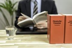 Advocaat in zijn bureau met boeken stock fotografie