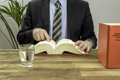 Advocaat in zijn bureau met boeken stock foto's