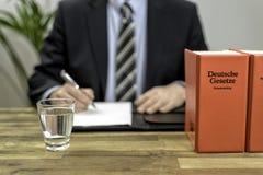 Advocaat in zijn bureau met boeken royalty-vrije stock foto's