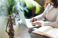 Advocaatbureau Standbeeld van Rechtvaardigheid met schalen en advocaat die aan laptop werken royalty-vrije stock afbeelding