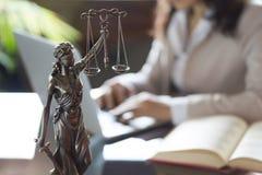 Advocaatbureau Standbeeld van Rechtvaardigheid met schalen en advocaat die aan laptop werken stock foto