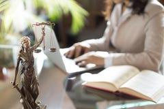 Advocaatbureau Standbeeld van Rechtvaardigheid met schalen en advocaat die aan laptop werken stock afbeeldingen