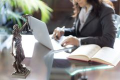 Advocaatbureau Standbeeld van Rechtvaardigheid met schalen en advocaat het werken stock foto's