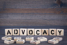 Advocacy word written on wood block. Dark wood background with texture.  stock images