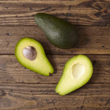 Advocados. Advocado halves on a wooden background Royalty Free Stock Photos
