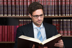 Advocate Reading Book At Courtroom. Young male advocate reading legal book at courtroom Royalty Free Stock Photos
