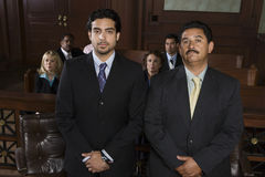 Advocate Standing With Client In Courtroom Stock Image