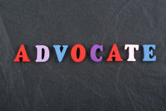 ADVOCATE word on black board background composed from colorful abc alphabet block wooden letters, copy space for ad text. Word on black board background composed Stock Image