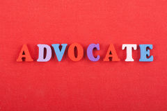 ADVOCATE word on red background composed from colorful abc alphabet block wooden letters, copy space for ad text. Word on red background composed from colorful Stock Photos