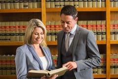 Advocaten die boek in de wetsbibliotheek lezen Stock Foto