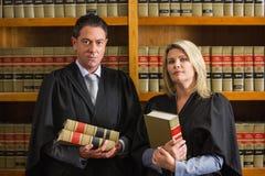 Advocaten die boeken in de wetsbibliotheek houden Stock Afbeelding