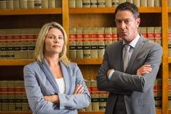 Advocaten die camera in de wetsbibliotheek bekijken Stock Foto