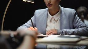 Advogado de defesa fêmea que interroga o suspeito nervoso, escrevendo seu testemunho filme