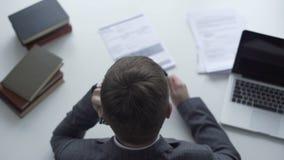 Advogado que fornece o conselho pelo telefone, corrigindo o relatório da investigação, vista superior vídeos de arquivo