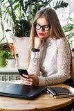 Advokat - den unga asiatiska kvinnaadvokaten som ser mobil smartphone och dricker kaffe från disponibelt pappers-, kuper Multietn Fotografering för Bildbyråer