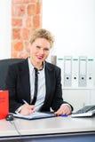 Advokat i regeringsställning med lagboken som arbetar på skrivbordet Royaltyfri Bild