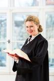 Advokat i regeringsställning med läsning för lagbok vid fönstret Arkivfoto