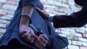 Advokat som arresterar brottslingen som på sätter handbojor, lag och beställning, brotts- bestraffning arkivfilmer