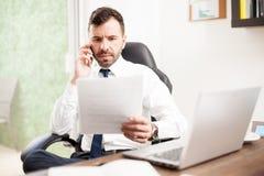 Advokat som granskar dokument över telefonen arkivfoto