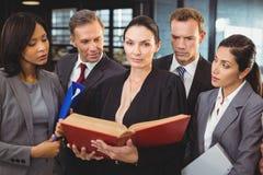 Advokat som läser en lagbok och påverkar varandra med businesspeople arkivfoto
