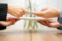 Advokaten ger den kvinnaavtalet och pennan till tecknet Fotografering för Bildbyråer